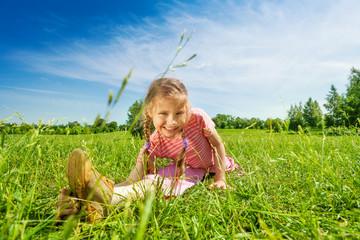Happy girl making leg-split on grass in summer