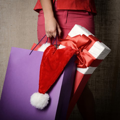 Beautiful young woman holding colored shopping bags, gift box an