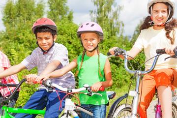 Three kids in helmets sitting on the bikes