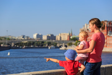 mother with kids looking at summer city