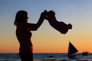 happy mother and baby having fun at sunset beach
