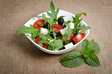 Greek salad in white salad bowl on sacking