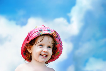 Happy little girl in a red hat on a background of blue sky with