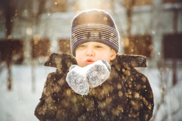 Little boy blows snow with mittens on bokeh background of snowfl