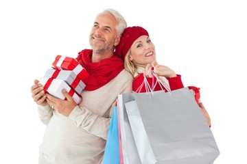 Smiling couple in winter fashion holding presents