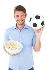Handsome young man holding ball and popcorn