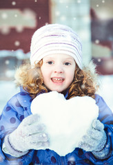 Beautiful little girl happily playing snowballs in winter park o