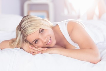Smiling relaxed young woman lying in bed