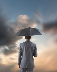 Composite image of businessman standing under umbrella