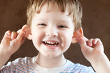 Happy Little boy, pulling himself on the ears