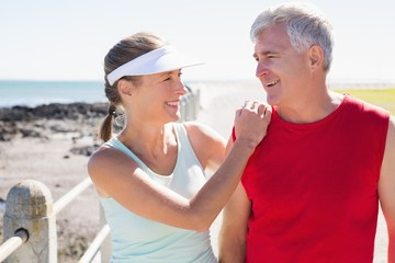 Fit mature couple warming up together on the pier