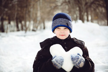 Charming child holding heart shaped snow in winter park.
