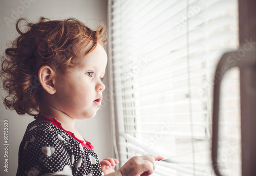 Little girl looking out the window through the blinds - 68752630
