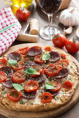 Italian food - pizza with salami and tomatoes, glass of wine