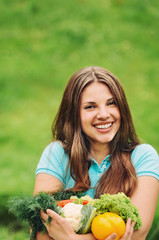 cute happy woman with organic healthy fruits and vegetables on t