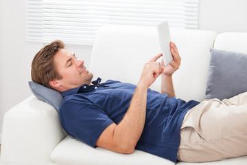 Man Using Digital Tablet While Lying On Sofa