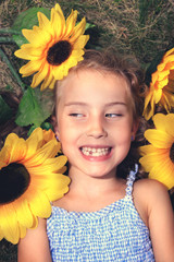 Joyful little girl lying on the grass with sunflowers