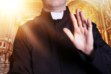 The priest at the church with raised hand