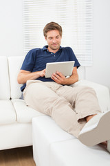 Relaxed Man Using Digital Tablet In Living Room