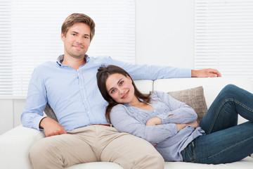 Happy Couple Relaxing On Sofa