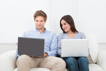 Couple Using Laptops At Home