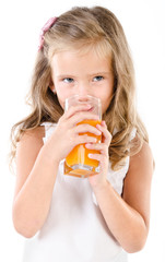 Cute little girl drinking orange juice isolated