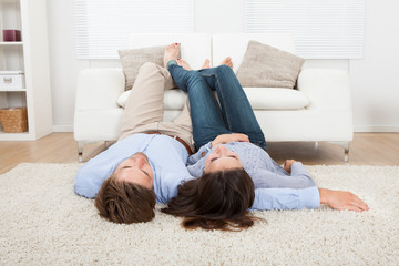 Couple Lying On Floor With Feet Up On Sofa