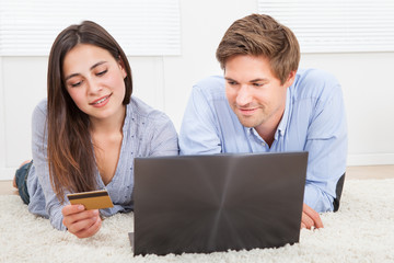 Couple Using Laptop And Credit Card To Shop Online