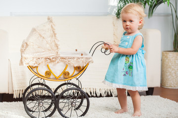 Little child is posing with small vintage pram