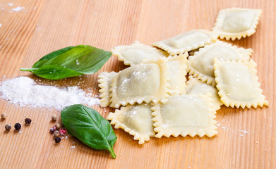 Homemade pasta ravioli with fresh basil, on wooden background