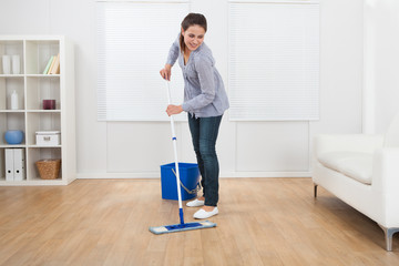Woman Cleaning Hardwood Floor Of Living Room