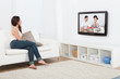 Woman Watching Television While Sitting On Sofa