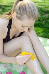 Twen im Bikini trägt Sonnenschutz auf