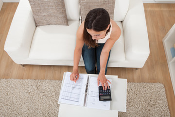 Confident Woman Calculating Home Finances At Table