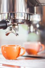 Single shot in orange cup of coffee