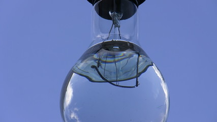 Electrical lamp bulb filled with water isolated on blue