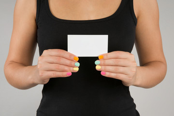 young girl with bright manicure keeps  business card in front of