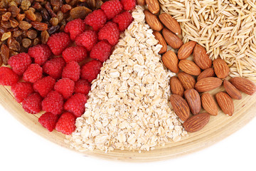 Big round plate with raisins, raspberries, oatmeal, nuts and