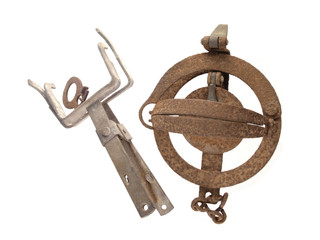 two old and rusty vermin traps on a white background.