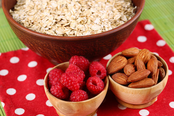 Big round bowl with oatmeal, nuts and raspberries