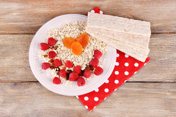 Big plate with oatmeal, small loaves of bread and berries