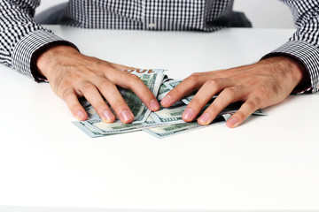 Closeup of a male hands hold dollars on the table