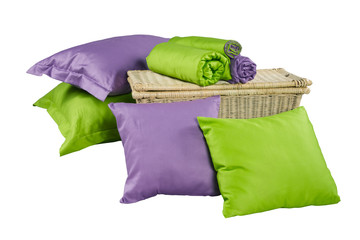 stack of colorful pillows and twisted blankets on basket isolate