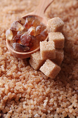 Reed sugar in wooden spoon on brown crystal sugar background