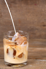 Iced coffee in glass on wooden background