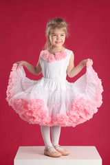 little girl dressed as a ballerina on a pink background