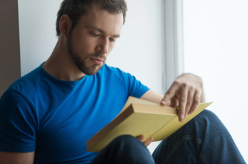 Young man sitting on window sill and reading.