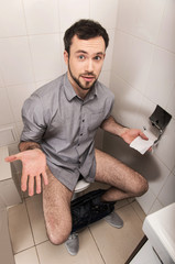 Close-up of man in toilet holding tissue.