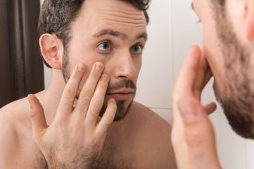 Closeup of young man examining his eye in mirror.