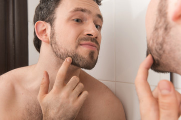 Closeup of young man examining his stubble in mirror.